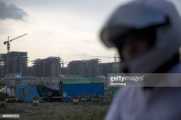 A motorcyclist rides past cranes operating at the One Park construction site developed by Graticity Real Estate Development Co in Phnom Penh Cambodia...