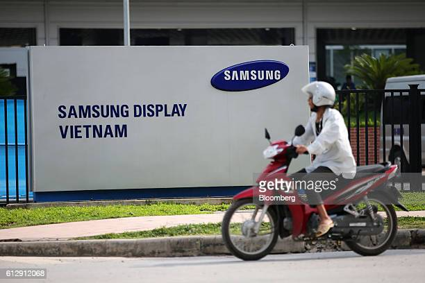 A motorcyclist rides past the Samsung Electronics Vietnam Co Plant at Yen Phong Industrial Park in Bac Ninh Province Vietnam on Thursday Sept 1 2016...
