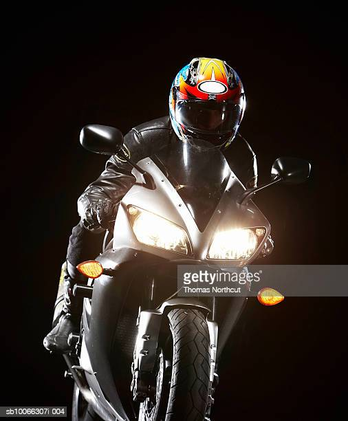 Motorcyclist riding motorbike with headlights on