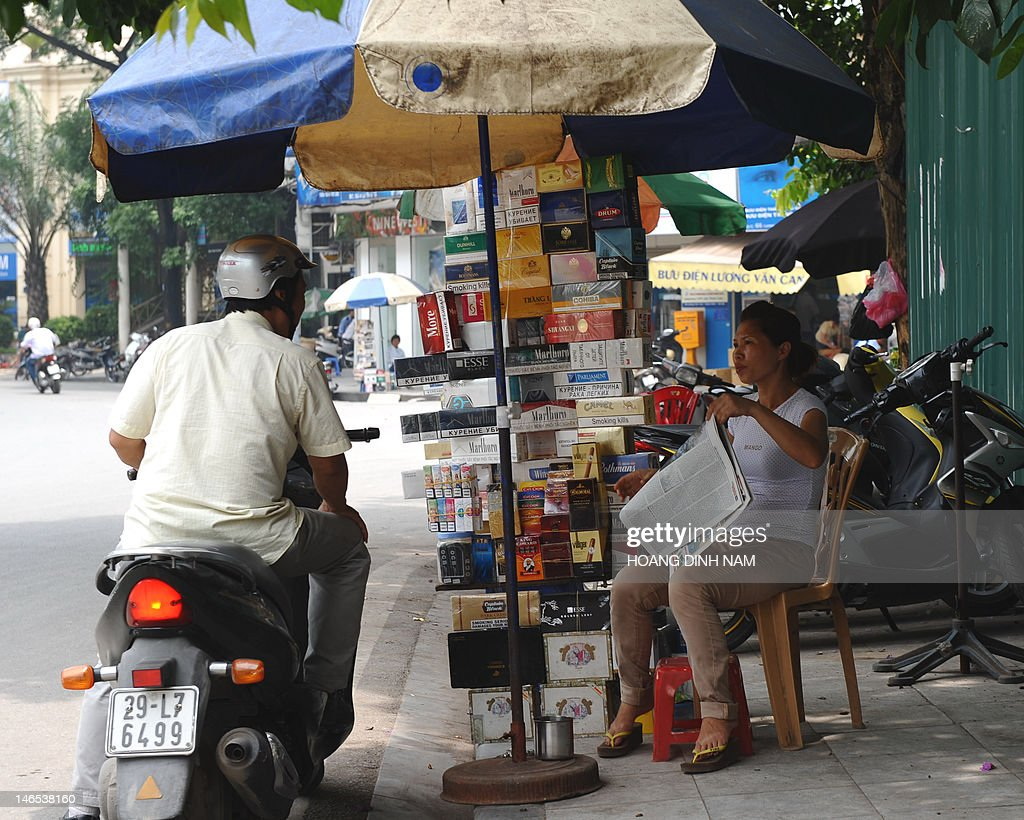 A motorcyclist stops to buy cigarettes from a street tobacco vendor in downtown Hanoi on June 19, 2012. Vietnam has passed a law banning smoking in pulic places and all tobacco advertising, an official said on June 19. AFP PHOTO/HOANG DINH Nam
