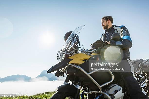 Motorcyclist taking a break on mountain pass, Tyrol, Austria