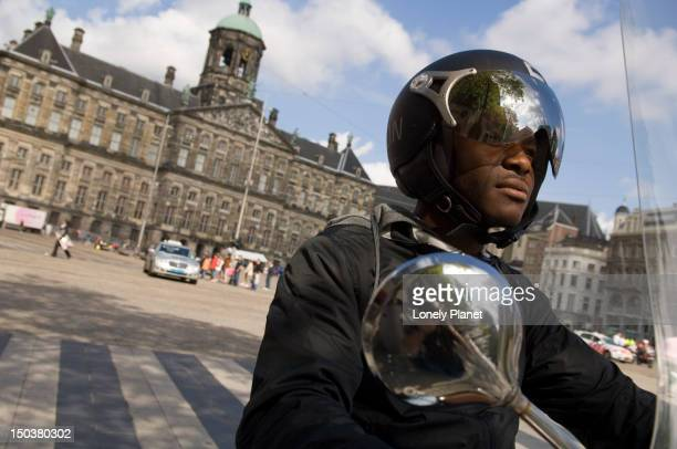 Motorcyclist travelling past Royal Palace.