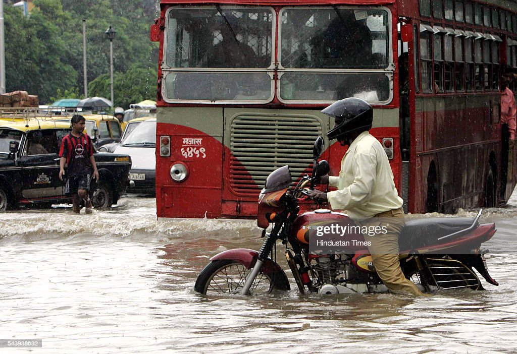 A motorcyclist wades through flooded streets after heavy rain showers at Naigaon on July 21, 2005 in Mumbai, India.