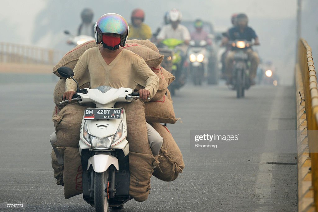 A motorcyclist wearing a mask crosses a bridge over the Siak river shrouded in haze in Pekanbaru, Riau Province, Indonesia on Friday, March 7, 2014. Indonesian central bank Governor Agus Martowardojo embarked on the country's most aggressive rate-increase cycle in eight years within a month of taking the helm in May to shore up the rupiah and damp price pressures. Photographer: Dimas Ardian/Bloomberg via Getty Images