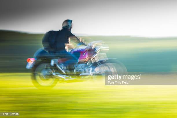 A motorcyclistis driving a summer evening