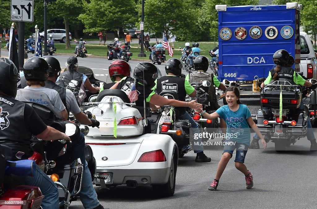 Motorcyclists a girl during the annual Rolling Thunder 'Ride for Freedom' parade ahead of Memorial Day in Washington, DC, on May 29, 2016. / AFP / MLADEN