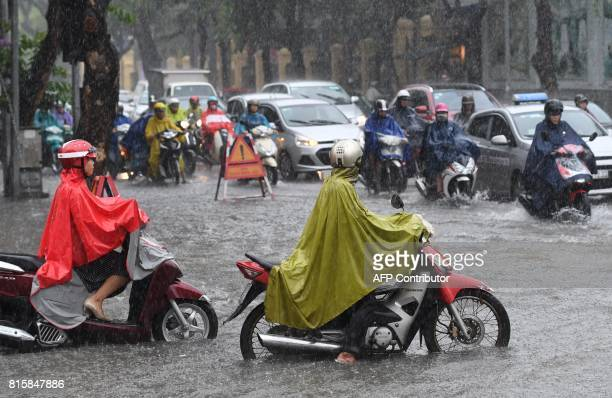 Motorcyclists and cars commute on a flooded street in Hanoi on July 17 after tropical storm Talas made landfall in northern Vietnam / AFP PHOTO /...