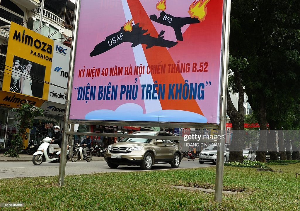 Motorcyclists and cars drive past a propaganda poster marking the 40th anniversary of 'Dien Bien Phu in the air' recalling Hanoi's battle against US massive bombing campaign carried out by the US Airforce strategic bombarders B-52 in December 1972, in Hanoi on December 7, 2012. Vietnamese Northern forces have claimed downing at that time some thirty four B-52 aircrafts. As parts of a propaganda programme on the event, Hanoi has organised workshops and exhibitions. AFP PHOTO/HOANG DINH Nam