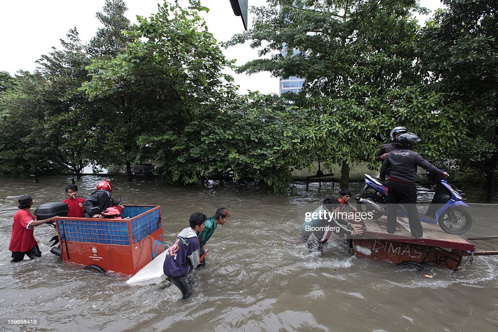 Motorcyclists are ferried through floodwaters on makeshift carts in Jakarta, Indonesia, on Friday, Jan. 18, 2013. Indonesia declared a state of emergency in Jakarta as flooding brought traffic to a standstill in the city of 9.6 million people and swamped the offices of President Susilo Bambang Yudhoyono. Photograph by: Dimas Ardian/Bloomberg via Getty Images