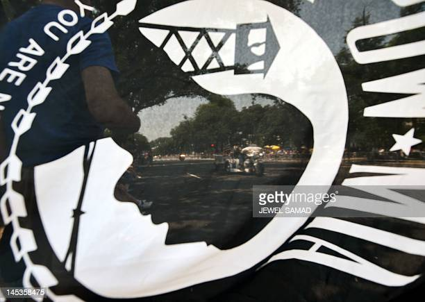 Motorcyclists are seen through a 'POW/MIA' flag during Rolling Thunder 2012 in Washington DC on May 27 2012 The 25th annual Rolling Thunder rumbled...