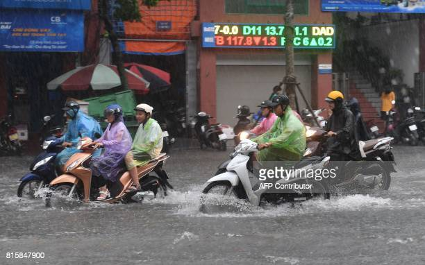 Motorcyclists commute on a flooded street in Hanoi on July 17 after tropical storm Talas made landfall in northern Vietnam / AFP PHOTO / HOANG DINH...