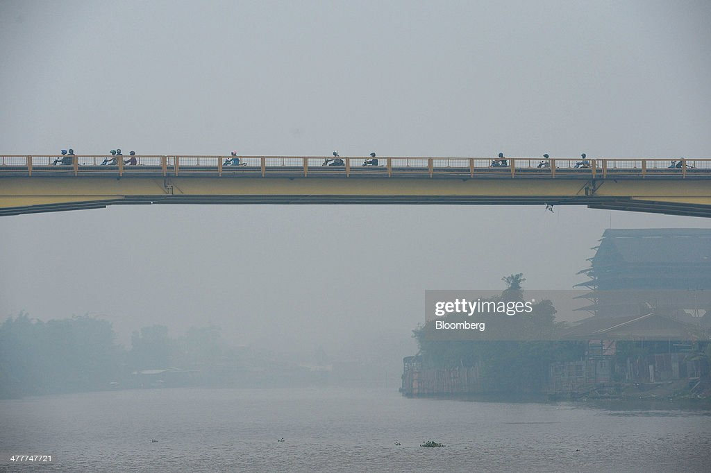 Motorcyclists cross a bridge over the Siak river shrouded in haze in Pekanbaru, Riau Province, Indonesia on Friday, March 7, 2014. Indonesian central bank Governor Agus Martowardojo embarked on the country's most aggressive rate-increase cycle in eight years within a month of taking the helm in May to shore up the rupiah and damp price pressures. Photographer: Dimas Ardian/Bloomberg via Getty Images