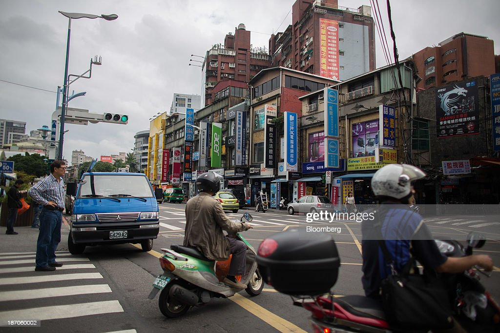 Motorcyclists cross an intersection in front of stores selling electronics, including Acer Inc. products, in Taipei, Taiwan, on Wednesday, Nov. 6, 2013. Acer, Taiwans second-largest computer maker, plunged to a 12-year low in Taipei trading after announcing a record loss, job cuts and the resignation of J.T. Wang as chief executive officer. Photographer: Lam Yik Fei/Bloomberg via Getty Images