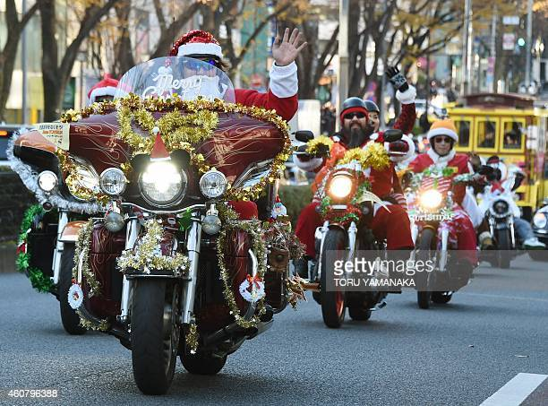Motorcyclists dressed in Santa Claus and reindeer outfits ride down the streets in downtown Tokyo during a Christmas 'toy run' by the Harley Santa...