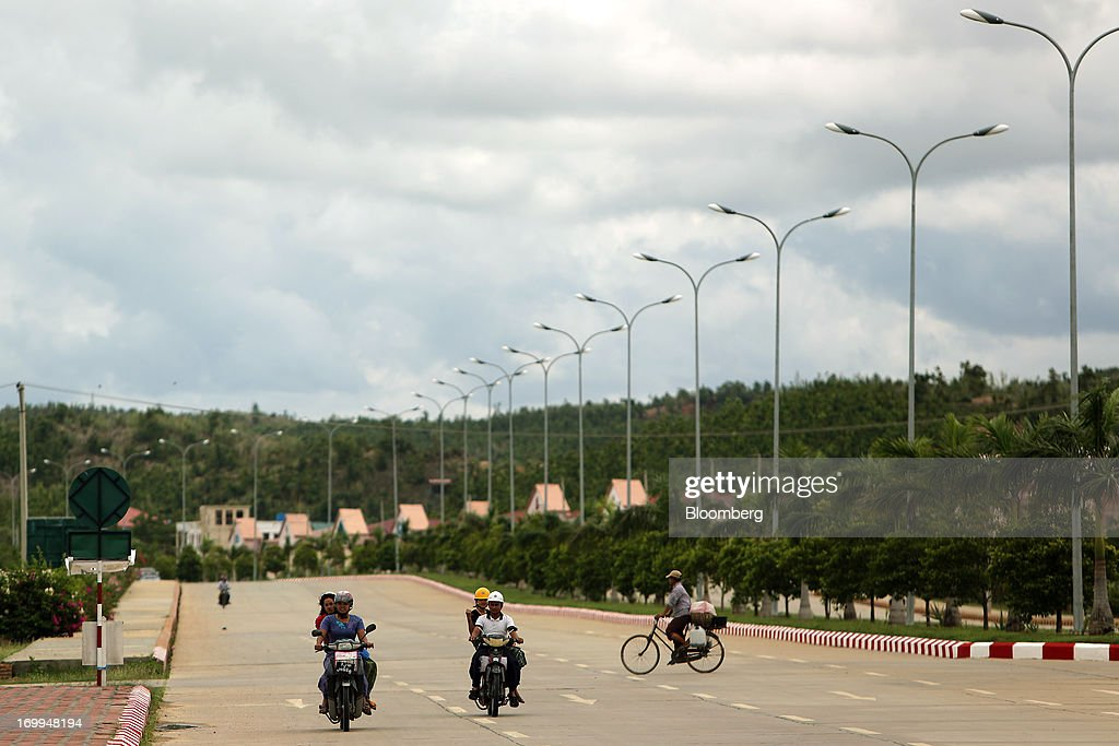 Motorcyclists drive along a road in Naypyidaw, Myanmar, on Wednesday, June 5, 2013. Myanmar hosts the three-day World Economic Forum on East Asia starting today, with heads of state and executives from companies including General Electric Co., Coca-Cola Co. and WPP Plc attending. Photographer: Dario Pignatelli/Bloomberg via Getty Images