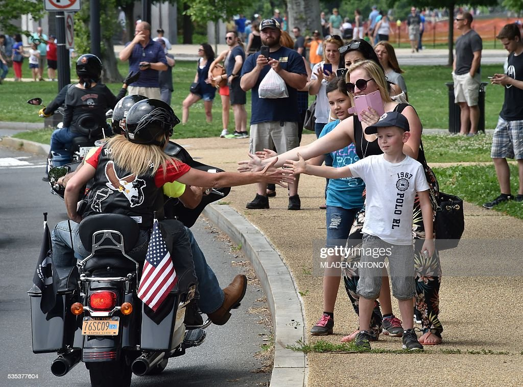 Motorcyclists greet bystenders during the annual Rolling Thunder 'Ride for Freedom' parade ahead of Memorial Day in Washington, DC, on May 29, 2016. / AFP / MLADEN