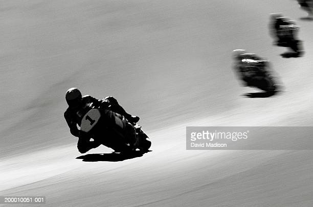Motorcyclists making turn on raceway (B&W, blurred motion)
