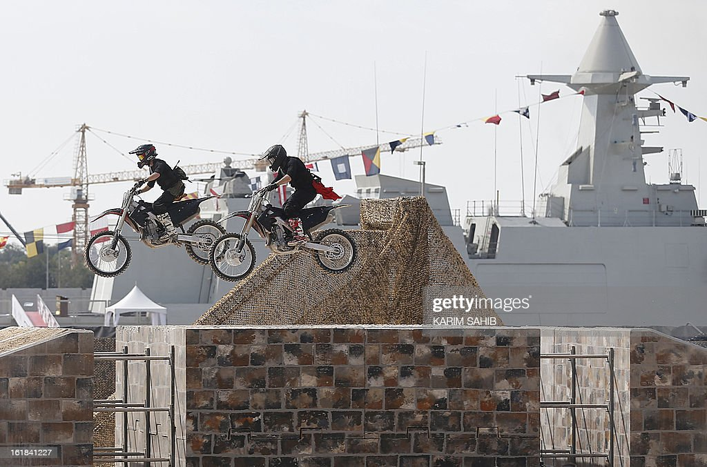 Motorcyclists perform stunts during the opening of the International Defence Exhibition and Conference (IDEX) at the Abu Dhabi National Exhibition Centre in the Emirati capital on February 17, 2013.