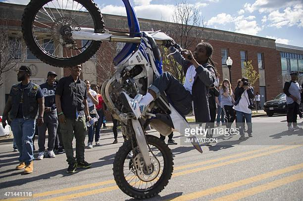Motorcyclists perform wheelies near demonstrators on W North Avenue in Baltimore Maryland April 28 2015 National Guard troops deployed to head off...
