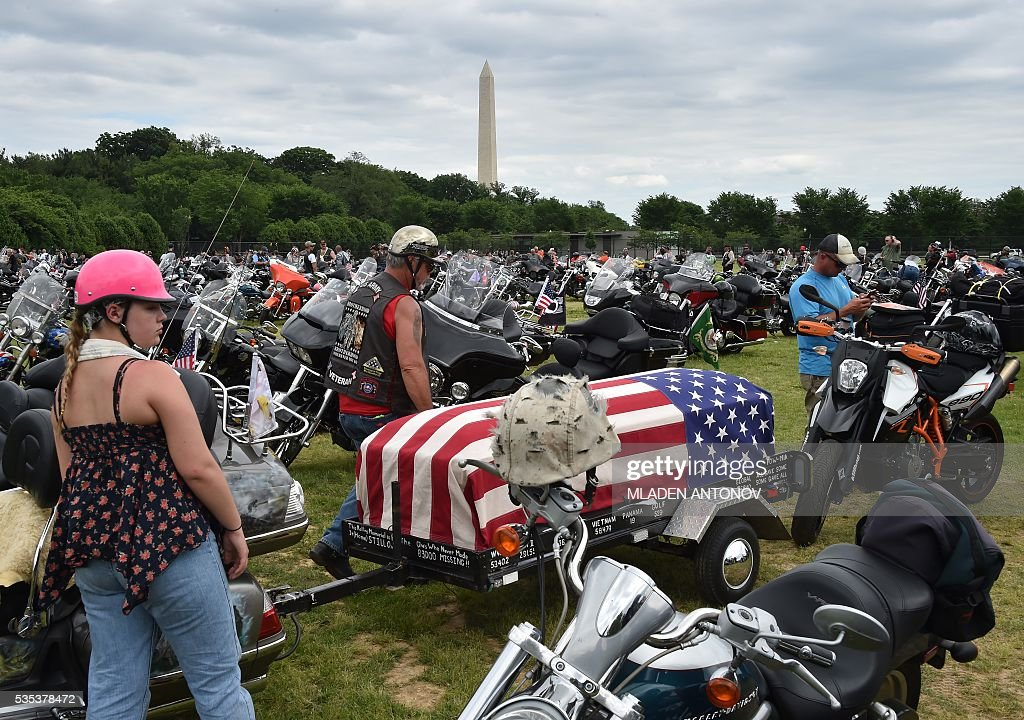Motorcyclists rest near their parked bikes during the annual Rolling Thunder 'Ride for Freedom' parade ahead of Memorial Day in Washington, DC, on May 29, 2016. / AFP / MLADEN