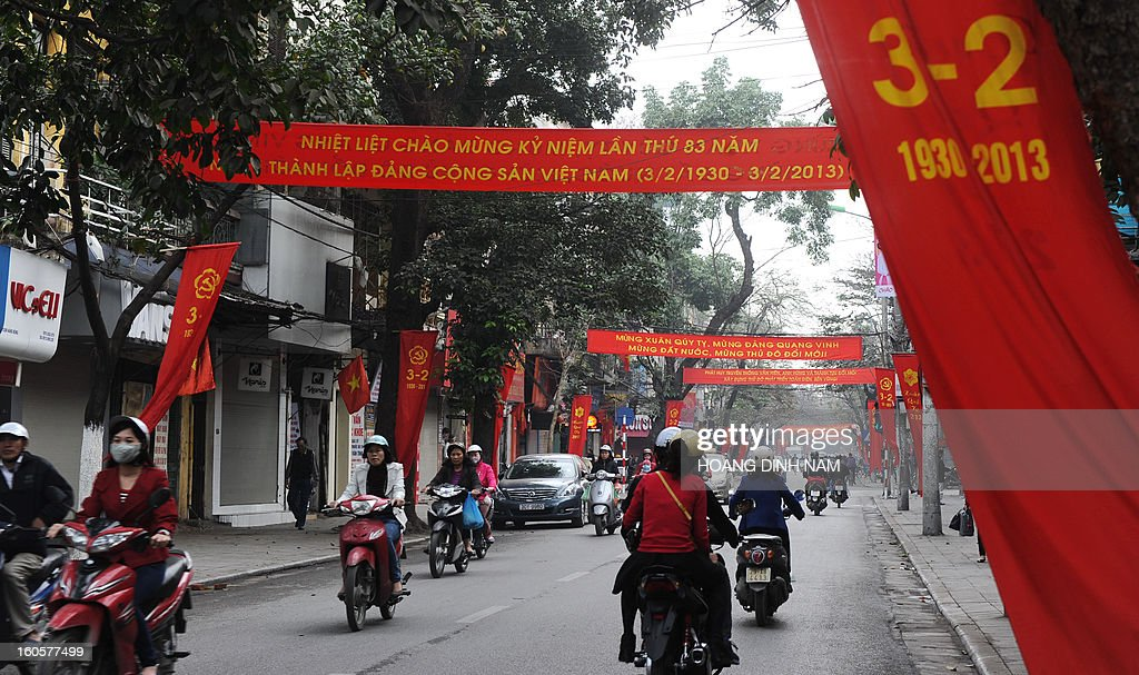 Motorcyclists ride amongst red banners marking the 83th anniversary of the foundation of the Vietnamese Communist Party (VC) in downtown Hanoi on February 3, 2013. The rulling communist party celebrates its anniversary at a moment ou the Southeast Asian nation faces a serious financial and economic crisis with state-run companies are used to criticism and now accused of creating a systemic economic crisis which the communist regime connot fix. AFP PHOTO / HOANG DINH Nam