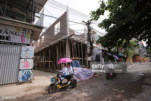 Motorcyclists ride past a building under construction in Ap Don hamlet Bac Ninh Province Vietnam on Thursday Sept 1 2016 Samsung Electronics Co and...