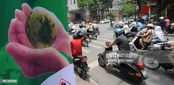 Motorcyclists ride past a climate change awareness poster hunged on a tree on a main street in downtown Hanoi on June 5 2009 on the occasion of the...