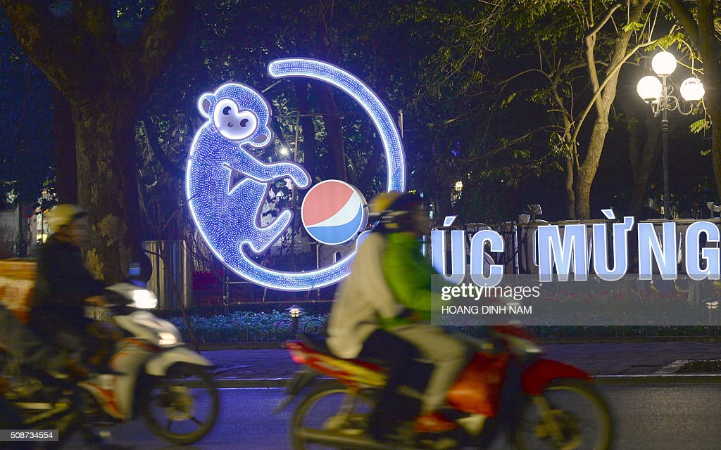 Motorcyclists ride past a decoration with the image of a monkey in downtown Hanoi on February 6, 2016 as people prepare to celebrate the Lunar New Year, or Tet. Vietnamese will mark the Lunar New Year, this year the Year of the Monkey in the Chinese Zodiac, along with many countries in east Asia, on February 8 . AFP PHOTO / HOANG DINH Nam / AFP / HOANG DINH NAM