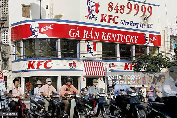 Motorcyclists ride past a Kentucky Fried Chicken restaurant in Ho Chi Minh City 22 March 2005 Vietnam's prime minister could visit the United States...