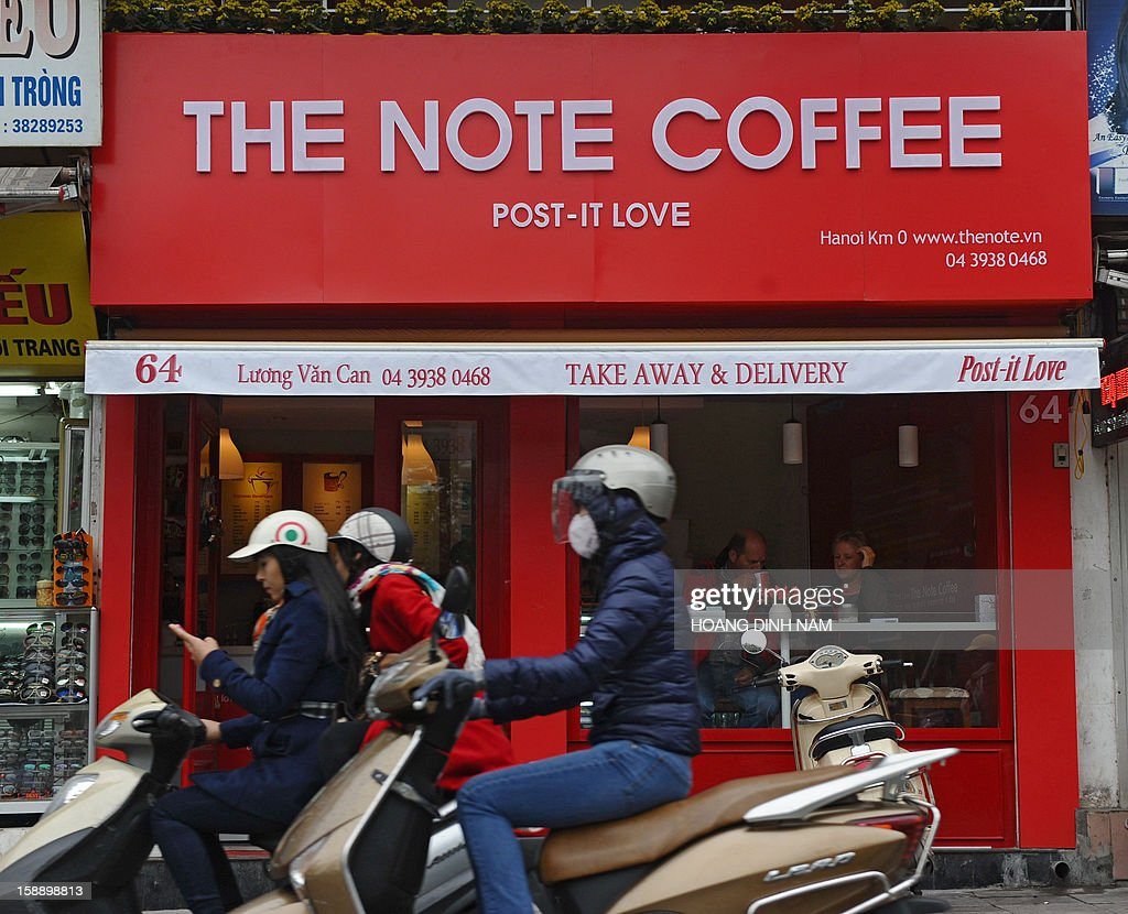 Motorcyclists ride past a newly opened coffee shop in downtown Hanoi on January 3, 2013. Starbucks said on January 3 it would open its first store next month in Vietnam, seeking a foothold in the coffee-loving country as part of efforts to expand in Asia. AFP PHOTO / HOANG DINH Nam