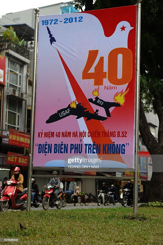 Motorcyclists ride past a propaganda poster marking the 40th anniversary of 'Dien Bien Phu in the air' recalling Hanoi's battle against US massive bombing campaign carried out by the US Airforce strategic bombarders B-52 in December 1972, in Hanoi on December 7, 2012. Vietnamese Northern forces have claimed downing at that time some thirty four B-52 aircrafts. As parts of a propaganda programme on the event, Hanoi has organised workshops and exhibitions. AFP PHOTO/HOANG DINH Nam