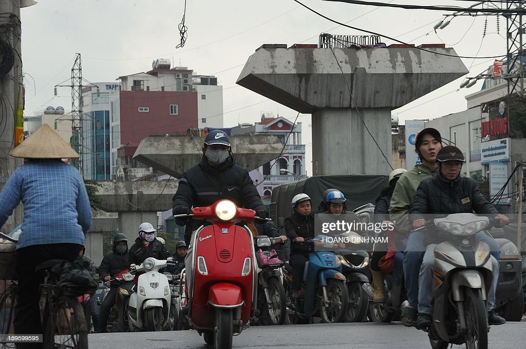 Motorcyclists ride past a row of concrete overhead skytrain supports, a delayed construction project in downtown Hanoi on January 17, 2013. The country faces growing worries about inflation, bank debts, falling foreign direct investment and a string of financial scandals among state-owned firms. AFP PHOTO/HOANG DINH Nam