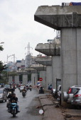 Motorcyclists ride past a row of concrete overhead skytrain supports a delayed construction project in downtown Hanoi on January 17 2013 The country...