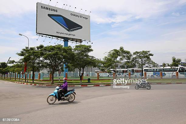 Motorcyclists ride past an advertisement for the Samsung Electronics Co Galaxy S7 Edge smartphone outside the Samsung Electronics Vietnam Co Plant at...