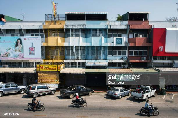 Motorcyclists ride past cars parked in front of low rise buildings in Nan Nan Province Thailand on Friday March 3 2017 After more than a year of...