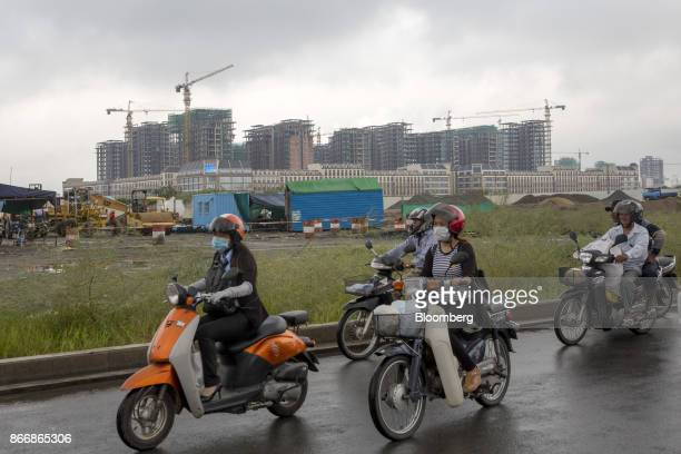 Motorcyclists ride past cranes operating at the One Park construction site developed by Graticity Real Estate Development Co in Phnom Penh Cambodia...