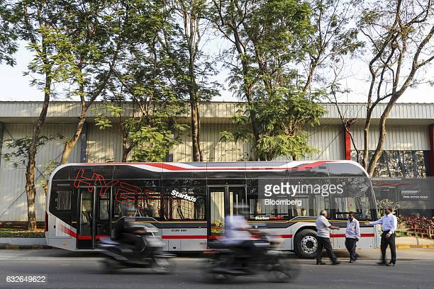 Motorcyclists ride past the newlylaunched Tata Motors Ltd Starbus Hybrid bus at the company's commercial vehicle manufacturing unit in Pune India on...