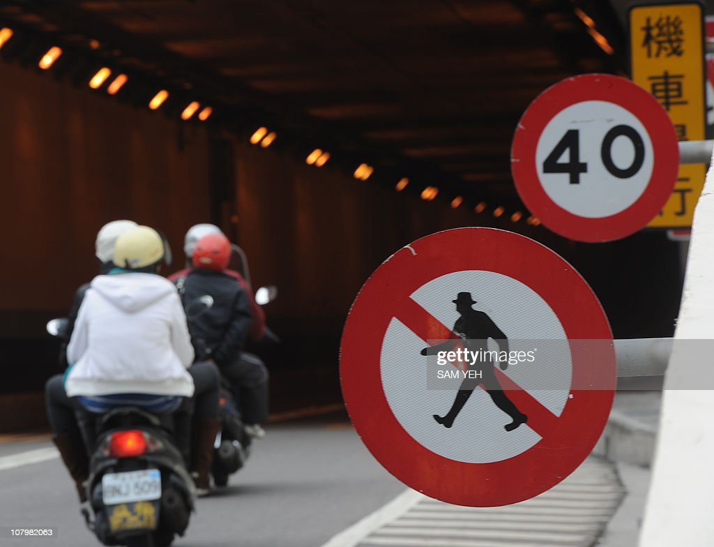Motorcyclists ride past traffic signs which are shown at the entrance of a tunnel in Taipei on January 5, 2011. AFP PHOTO / Sam YEH