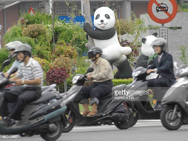 Motorcyclists ride past two panda models recently erected outside Taipei's Sungshan airport on October 13 2008 Taiwan's Chinafriendly Kuomintang...