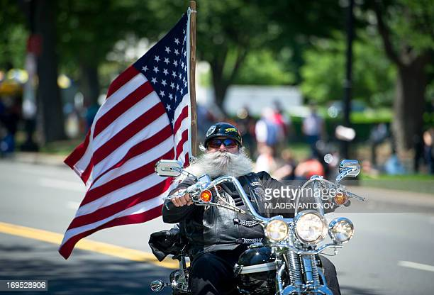 A motorcyclists rides waving a US flag during Rolling Thunder 2013 in Washington on May 26 2013 The 26th Annual Rolling Thunder rumbled into he US...