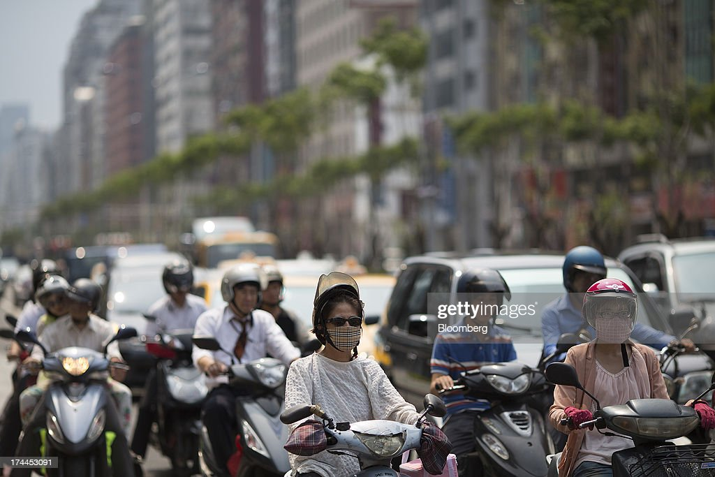 Motorcyclists sit next to vehicles in traffic on Hsin Yi Road in Taipei, Taiwan, on Wednesday, July 24, 2013. Taiwan President Ma Ying-jeou ruled out driving down the Taiwan dollar to boost exports following the currencys rally against the yen and said the government still aims for growth of at least 2 percent this year. Photographer: Jerome Favre/Bloomberg via Getty Images
