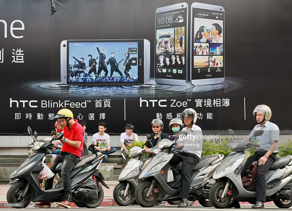 Motorcyclists stop at an intersection in front of an advertisement for HTC Corp.'s One smartphone in Taipei, Taiwan, on Thursday, July 4, 2013. HTC is scheduled to announce second quarter earnings on July 8. Photographer: Maurice Tsai/Bloomberg via Getty Images