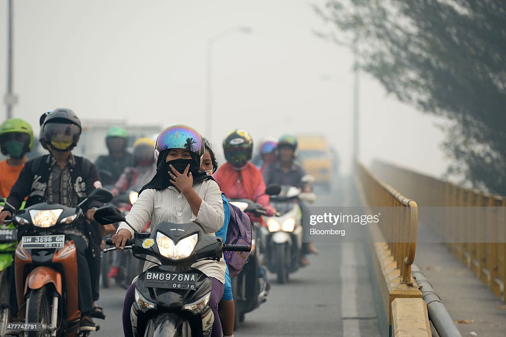 Motorcyclists wearing masks cross a bridge over the Siak river shrouded in haze in Pekanbaru, Riau Province, Indonesia on Friday, March 7, 2014. Indonesian central bank Governor Agus Martowardojo embarked on the country's most aggressive rate-increase cycle in eight years within a month of taking the helm in May to shore up the rupiah and damp price pressures. Photographer: Dimas Ardian/Bloomberg via Getty Images