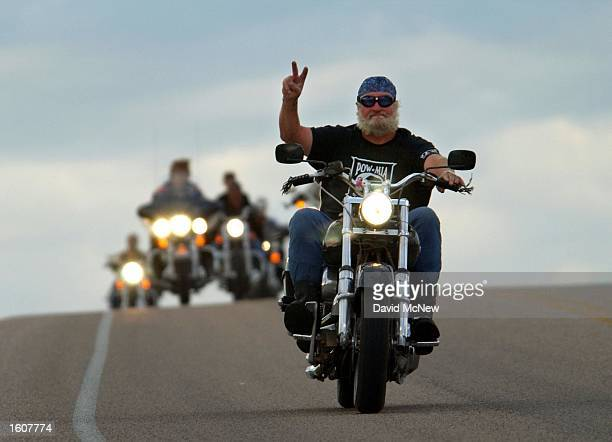 A motorcylist gives a hand signal while on a run near Devils Tower National Monument WY which is one of many popular destinations for cyclists...