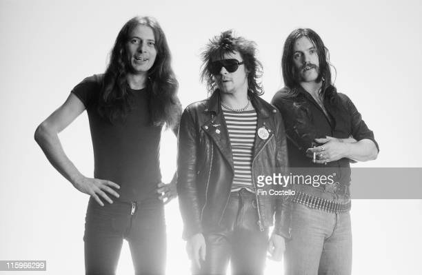 guitarist Eddie Clarke drummer Phil Taylor and singer and bassist Lemmy Kilmister British heavy metal band pose for a group studio portrait against a...