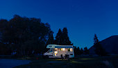 Motorhome on campsite at night. Can use for summer or holiday concept background.