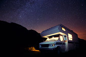 A small illuminated motorhome at night under the stars.
