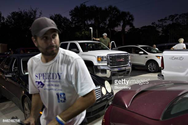 A motorist center back stands in his vehicle and tries to calm a neighboring motorist after police shut down the gas station due to a county wide 8PM...
