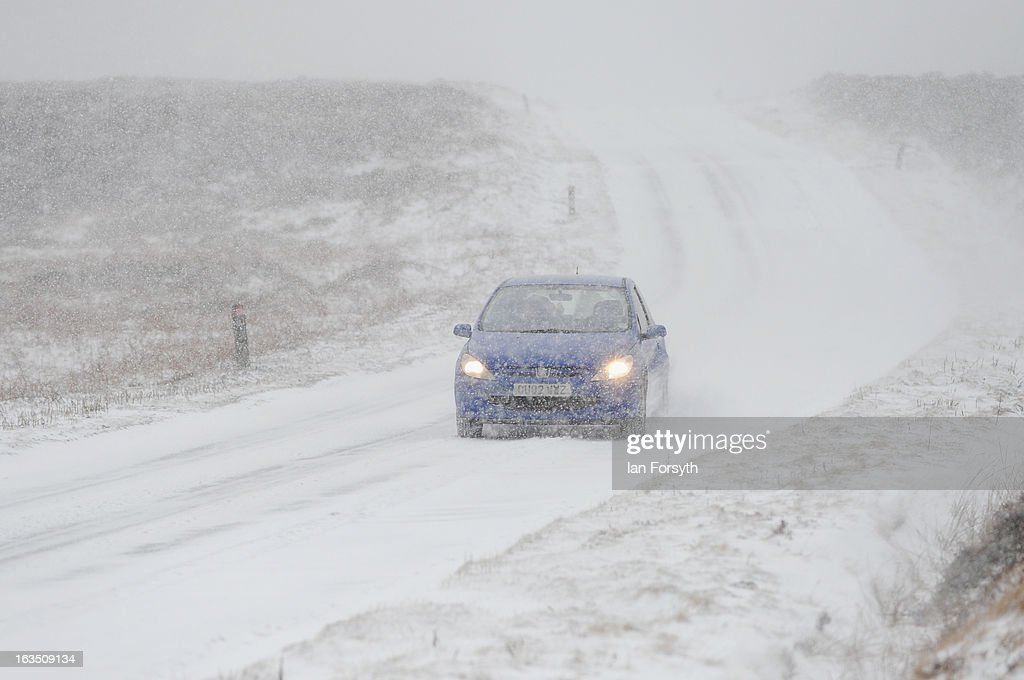 A motorist drives on a snow covered road as brief but heavy snow storms move across the Yorkshire Moors on March 11, 2013 in Yorkshire, United Kingdom. Wintery weather returned to the UK as snow fell across many parts of the country, with a number of weather warnings being issued.