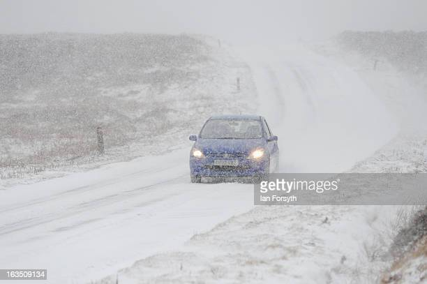 A motorist drives on a snow covered road as brief but heavy snow storms move across the Yorkshire Moors on March 11 2013 in Yorkshire United Kingdom...
